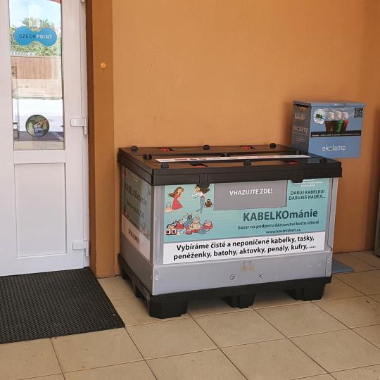 Sběrná nádoba na kabelky umístěná před vchodem do budovy OÚ